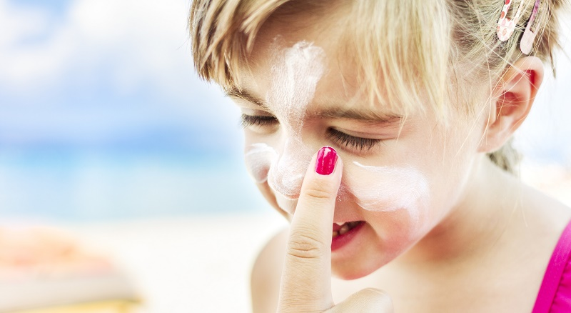 Applying sunscreen to child's face