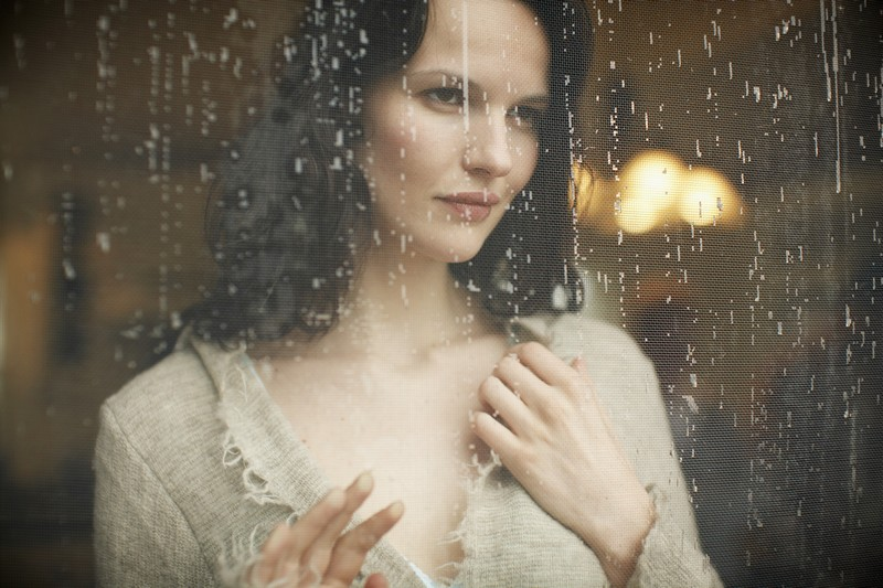 Serious Woman Looking Through Window With Rain Running Down --- Image by © amanaimages/Corbis