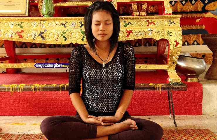 Donna medita a gambe incrociate