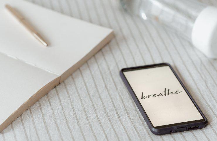 Smartphone con scritto breathe e quaderno con penna