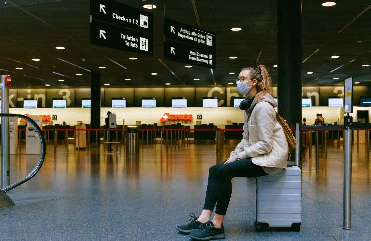 Ragazza con mascherina anti covid seduta su una valigia in aeroporto deserto