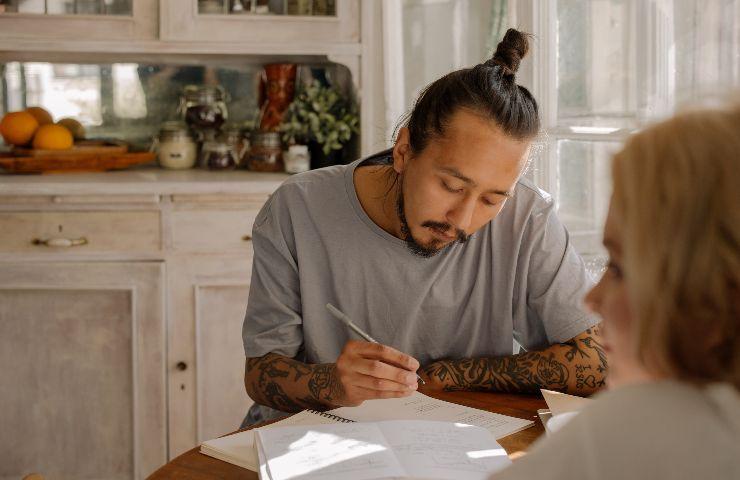 Un ragazzo asiatico studia su un tavolo