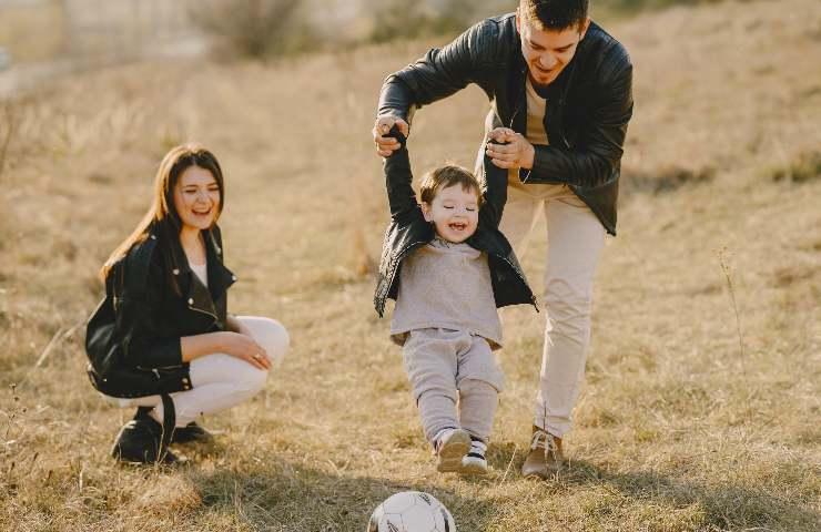 Un padre solleva le braccia del figlio insieme alla madre che li guarda divertita