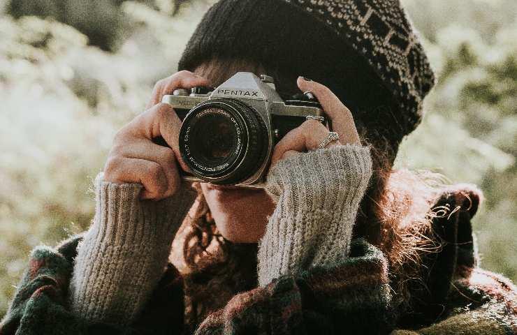 Donna con macchina fotografica e sguardo sull'obbiettivo