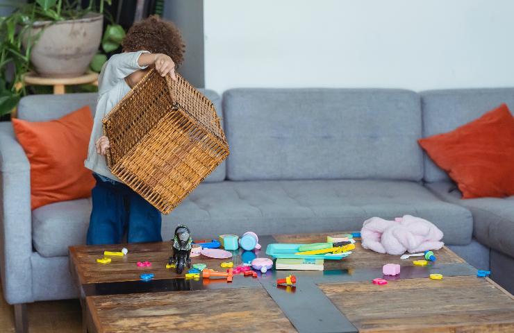 Bambino ribalta una cesta di giochi sul tavolo