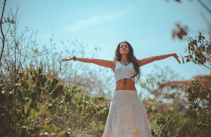 Donna con braccia aperte in mezzo alla natura
