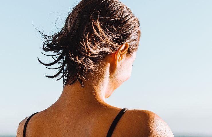 Donna girata di schiena prende il sole in costume da bagno