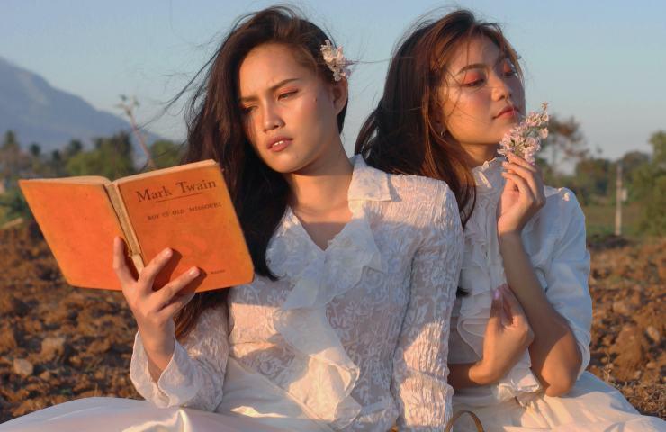 Ragazze asiatiche leggono un libro in mezzo a un campo