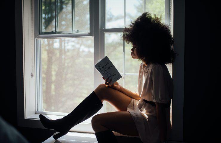 Ragazza afroamericana legge un libro seduta sul bordo della finestra