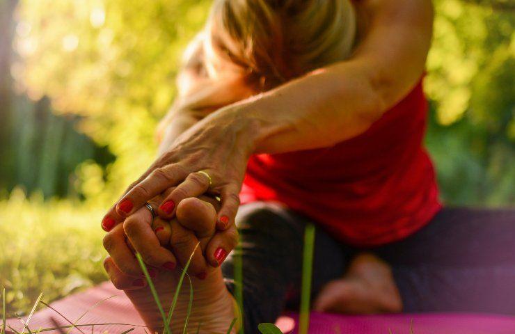 Donna in allungamento su gamba destra, effettua esercizi di stretching