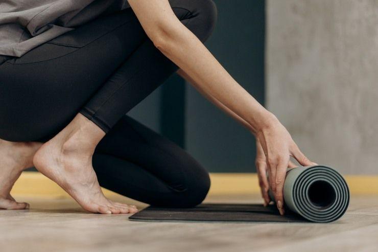donna con tappetino per lo yoga